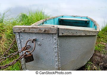 An old green iron boat chained up on the lake shore in summertime