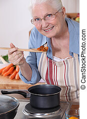 An old lady cooking.