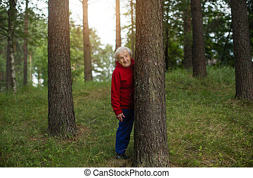 An old lady in a red jacket walks in a pine Park