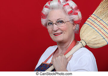 An old lady with hairroller on and a broom.