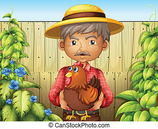 An old man holding a rooster near the wooden fence