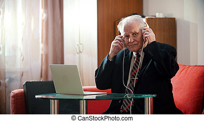 An old man is holding headphones with his hands and listen the music