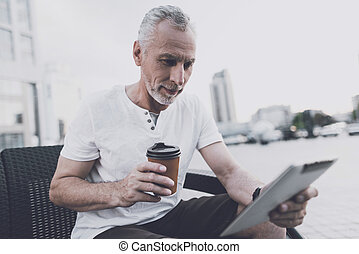 An old man with a beard sits on a sofa in the street. He is holding coffee and a tablet