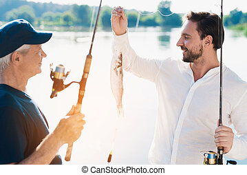 An old man with a spinning stands in front of a man who shows him the fish he just caught
