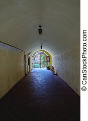 An old medieval stone tunnel under fortress wall with a garden and light at the end.