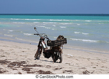 An old motorcycle is on the sand at the beach.