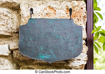 an old plate hang on the stone wall