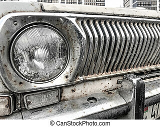 An old retro vintage hipster rusty oxidized chrome-plated metallic silver radiator grille and a round glass retro spotlight of an antiquan white white American car from the 60s, 70s, 80s, 90s, 2000s