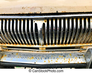 An old retro vintage hipster rusty oxidized chrome-plated metallic silver radiator grille in front of the retro hood of an antiquana white American passenger car from the 60s, 70s, 80s, 90s, 2000s