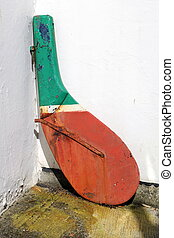 An old rudder from a fishing boat or rawler, being used as a decorative item in a back yard