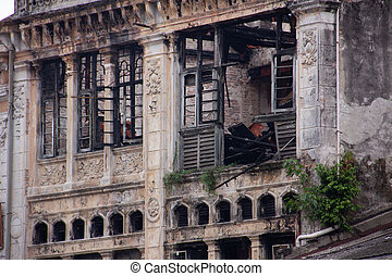An old ruined hystorical building with traces of fire, soot on the walls near the windows.
