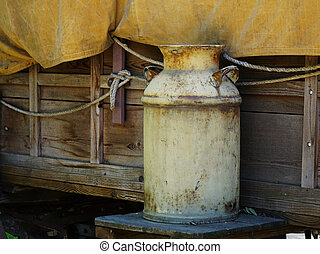 Old rusty milk can sitting outside a covered wagon.