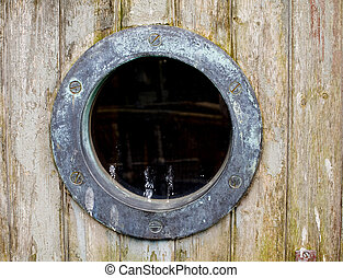 An old rusty ship port hole against a wood background