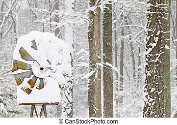 An old rusty snow covered windmill outside in the woods on a cold snowy and frigid winter day with room for your text.