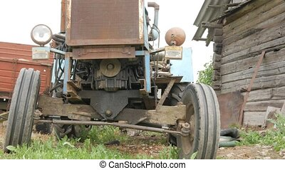 An old rusty tractor stands near the field. The machine for agriculture is waiting for the processing of the field