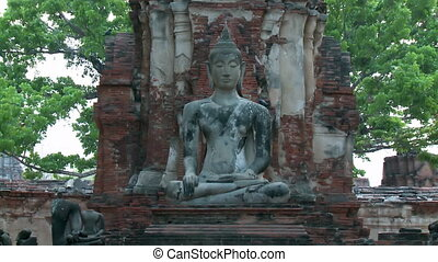 A medium, steady shot of a sandstone sculpture of a sitting Buddha at the base of a Prang brick structure surrounded by headless statues.