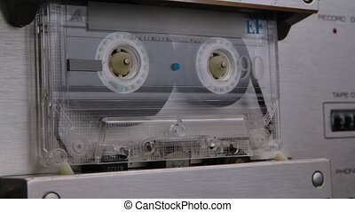 An old shabby compact audio cassette spins in a tape recorder. Detailed macro shot of a vintage tape recorder. Listening to nostalgic music from the 90s. Close up. Slow motion