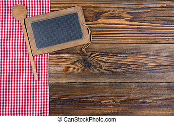 An old slate board together with a wooden spoon lies on a red and white chequered cloth on a rustic wood background with text space for your own design.