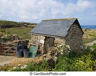 An old stone built shack in a rural setting