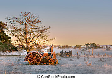 old tractor - an old tractor lays in the field on a cold and...