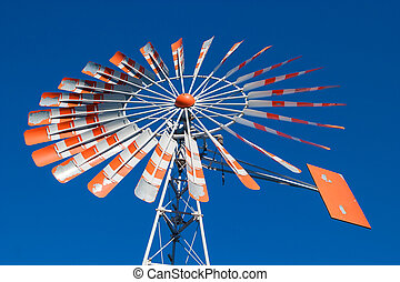 An old windmill with a cloudless blue sky