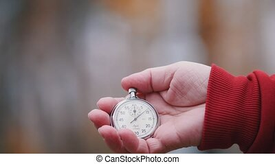 An old woman is holding a pocket watch. Close up