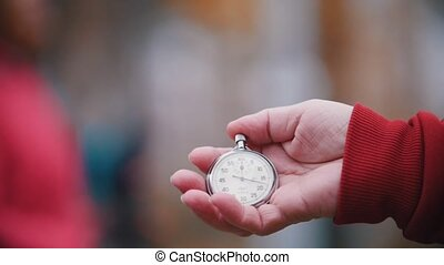 An old woman is holding a pocket watch. Slow motion