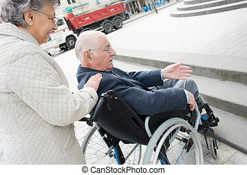 an old woman is pushing husband in wheelchair