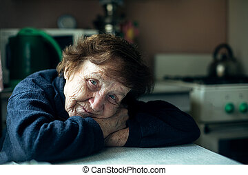 An old woman is sad in the kitchen of her house.