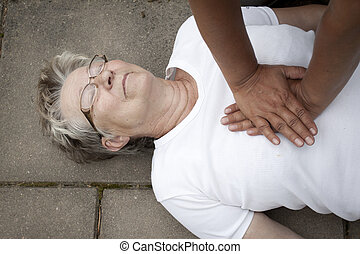 an old woman receiving firs aid - A senior lade with cardiac...