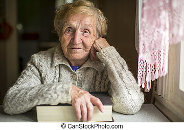 An old woman sitting with a book