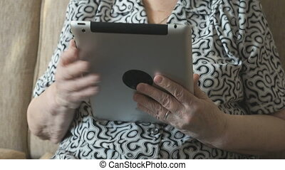 An old woman viewing photos using a digital tablet