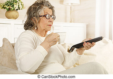 An old woman with a TV remote in her hand