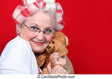 An old woman with hair rollers on hugging a teddy bear.