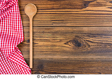 An old wooden spoon and a red and white chequered cloth lie on a rustic wooden background with text space to design yourself.