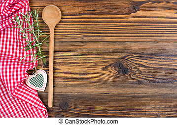 An old wooden spoon, decorative heart and rosemary twigs and a red and white chequered cloth lie on a rustic wood background with text space to design yourself.