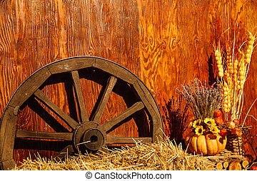 An old wooden wagon wheel stands in the hay.
