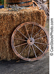 An old wooden wheel from a cart near a haystack.The village, the village decor.