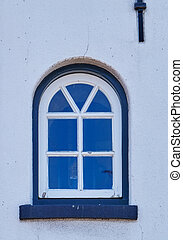 An old wooden window of a lighthouse. The green and white paint is peeling off. A classic semi-circular arched window in a white wall with iron lightning conductors
