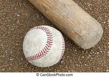 An old worn baseball and bat in a field