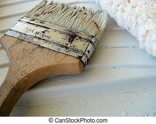 An old worn out painter\'s brush and roller in a painting...