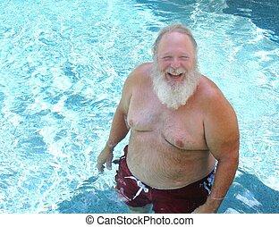 A robust elderly man who looks like Santa Claus enjoys a swim on a hot summer day.
