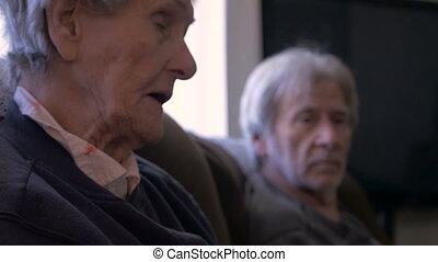 An older woman and her senior son visit while laughing and...