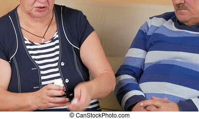An older woman gives a pill with a glass of water to her husband at home on the couch.