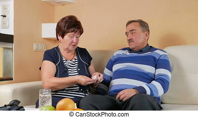 An older woman gives a pill with a glass of water to her husband at home on the couch. Poor man's well-being. Taking care of his wife about her husband