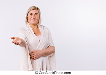 An older woman with a sweet smile points at the camera against a white background with empty side space.