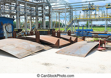 An open-air production site at an industrial plant, a workshop for welding large iron metal barrels and containers made of metal sheets. Manufacture, construction of equipment