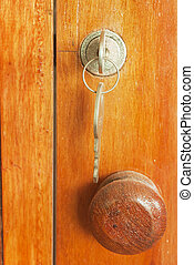 an open antique door with key in the lock