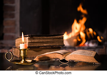 Bible with a burning candle - An open Bible with a burning ...