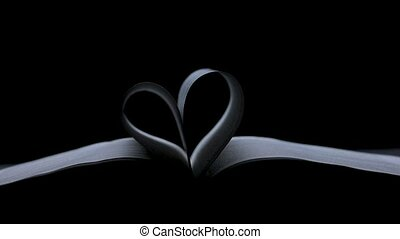 An open book lies in a dark studio on a black background. The pages of the book are folded in the shape of a heart. Valentine's day concept. Slow motion. Close up
